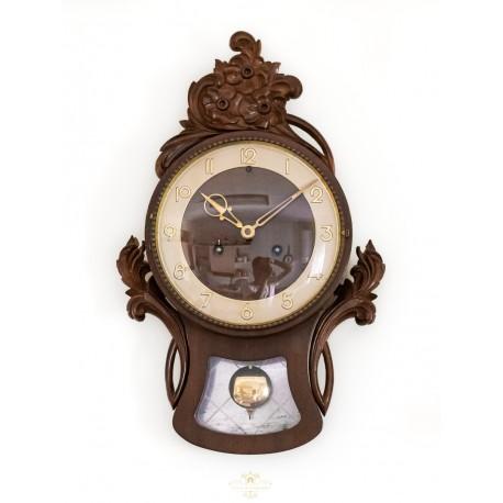 Clásico reloj de pared de madera,funcionando con cuerda manual.